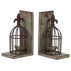 """Set of two weathered bookends with fleur-de-lis adorned birdcages.Product: Set of 2 bookendsConstruction Material: Resin Color: Grey and brown Dimensions: 10"""" H x 4.25"""" W x 6"""" D eachCleaning and Care: Wipe with clean damp cloth"""