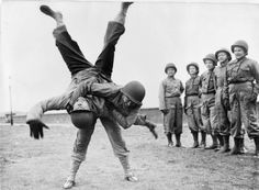 Lieutenant Louise Erman of the US Army Nurse Corps throwing her Ju-Jitsu instructor Major Strom during an unarmed combat class.  The Army Nurses were put through rigiours training in preperation for the opening of the second front—Normandy—by the Allies where they would follow the landing forces to help the wounded.