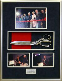 A shadowbox of the ceremonial ribbon cutting scissors and photos from the opening day at the Atlanta Aquarium.