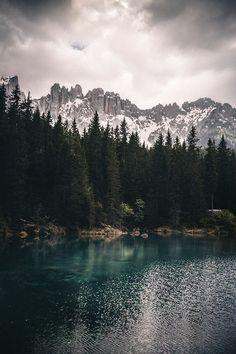ITALY –  Karersee lake (Lago di Carezza), Trentino-Alto Adige/Südtirol (South Tyrol) region. In the background is the Latemar mountain. https://www.google.ca/maps/place/Karersee/@46.4092446,11.5050078,12z/data=!4m5!3m4!1s0x47786fe8e28162b7:0xdb332cfdd84fb462!8m2!3d46.409225!4d11.5750671