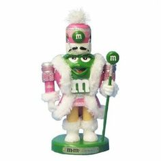 """8.3"""" M&M Nutcracker Color: Green by Kurt Adler. $34.99. MM6122M. Little Girl Soldier Dressed in Pink. Kurt Adler Green M&M Wood Nutcracker. Made of. Approximately 8.25"""" Tall. MM6122M Color: Green Features: -Standing in a traditional red and gold nutcracker soldier uniform.-M&M grins with a fluffy white goatee and holds a glittering M&M staff."""