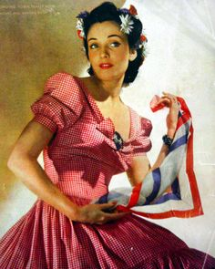 1940 Vogue UK red white plaid gingham dress day peasant picnic casual puff sleeves bow front full skirt color photo print ad hair flowers scarf 40s vintage fashion style