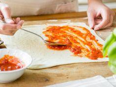 Pizzasauce auf Pizzateig verstreichen