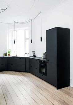 Modern kitchen with cabinetry and drawer fronts in black linoleum and integrated pulls/cut outs for handles. We love the bright hardwood floors.