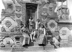 Empat wanita Bali dengan seorang pria Eropa di depan pintu masuk kompleks pura di Bali, sekitar 1935