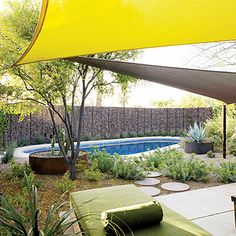 Yellow and gray shade sails overhead provide much-needed respite from sun, and Richard Serra–esque steel planters balance the heft and drama of the river-rock wall. A generous sprinkling of plants adds softness.