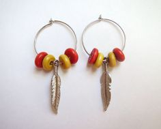 Red and yellow wooden bead hoop earrings with silver feather charms by Emerald City Custom Jewelry.