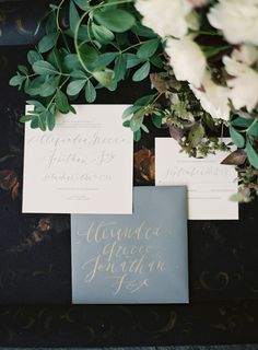 Slate-blue envelopes with gold calligraphy