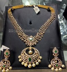Brilliant cut diamonds adorned 22 carat gold metal huge diamond necklace with chand bali design pendant merged in the center. Studded with round emeralds, …