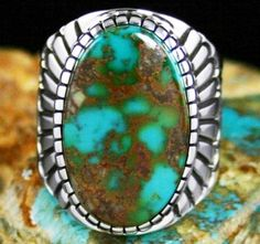 Alton Bedonie Rare Gem Grade Royston Spiderweb Turquoise Ring #AltonBedonie This incredible ring features rare gem grade natural two tone Royston turquoise. The gem is electric blue green with rusty reddish-chocolate-brown spiderweb matrix. The cabochon is set in Alton's signature high hand chiseled bezel which blends into a prayer feather pattern deeply stamped on the extra heavy shank. Fine thin lines and  texture work on either side further compliments the beauty of the stone. The…