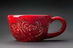 Red ceramic hand carved teacup with a heart and a bow by Landby