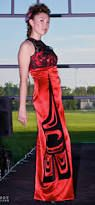 Lyn Kay Designs..Red bridal satin gown with black lace overlay on bodice with Coast Salish feather down one side and back slit.