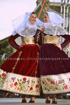 photo: two women wearing Sardinian traditional costume while dancing ...