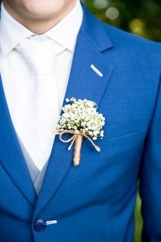 Groom outfit in blue suit white tie and baby's breath button hole flower
