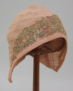 Cloche hat of beige straw.  The cloche is based on a Phrygian cap, although lacking the forward-pointing section at top. It is of crocheted beige straw thread.  The crown is rounded, coming to a gentle point at to, and with sides that extend downwards to cover the ears.  At the front is a crescent-shaped panel of printed chiffon which extends back and down sides of hat.  The panel is printed with an abstract floral/foliate design in greens, reds, blues, and golds on a beige ground…
