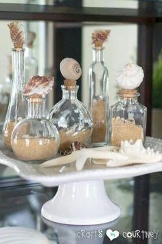 Add saw shells and sand to clear glass bottles.
