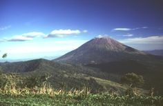 Conical San Miguel volcano, one of El Salvador's most prominent landmarks, rises across a low saddle SE of Chinameca (Pacayal) volcano. The 2130-m-high San Miguel is seen here from Cerro el Limbo, a cone on the western flank of Chinameca. The southern side of Chinameca's 2-km-wide summit caldera is visible at the left.