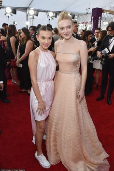 Stranger Things star Millie Bobby Brown (l) paired her blush halter Calvin Klein Pre-Spring 2018 dress with twin buns and Converse sneakers; posing with Dakota Fanning (r) who wore a Prada gown Millie Bobby Brown, Bobby Brown Stranger Things, Divas, Sag Awards, Dakota Fanning, Bridesmaid Dresses, Wedding Dresses, Queen, Celebs