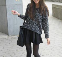 Black and white patterened sweater, black flowy skirt, sheer black nylons and a black handbag!