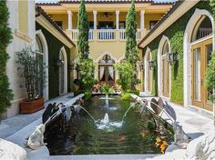 Florida's designer-owned 'Palace of the Eagles' has stone paving, arched openings, covered balconies, a linear pond, carved stone sculptures, ivy covered walls, and spanish tile roofing.