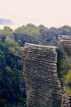Pancake Rocks, Paparoa NP,  S Island, NZ.. The Pancake Rocks are a heavily eroded limestone area where the sea bursts through several vertical blowholes during high tides. Together with the 'pancake'-layering of the limestone (created by immense pressure on alternating hard  soft layers of marine creatures  plant sediments), these form the main attraction of the area.