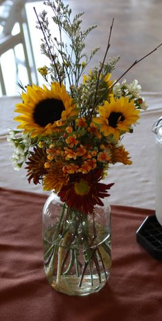 Simple autumn mason jar centerpiece with sunflowers at a fall party. Maneeley's Lodge in South Windsor, CT.
