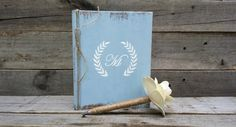 Personalized Rustic Wedding Guest Book with Twine Wrapped Flower Pen. This nice size distressed hardcover guest book would be perfect for your guest to sign at your wedding, bridal shower, or to leave advice for the newly married couple. Also perfect for anniversaries or birthdays.  **At checkout please leave the initial and if you would like the book a different color**  Details.. *Hardcover book *Measures 8x6 *Initial adorns the front with wedding quote on first page *60 acid free white…