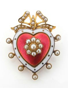 An Edwardian heart shaped brooch pendant, centred with a cluster of seed pearls on pink enamel ground and within a white enamel border. Surmounted with a seed pearl set bow and further border of pearls. Closed compartment to the reverse. 3.7cm wide.