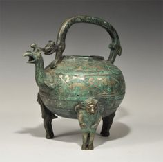 An undated archaistic cast vessel with bulbous body, three short legs, carrying handle and spout; the legs formed as anthropomorphs; the body with concentric bands of gilt geometric designs; the handle formed as a canine with open mouth and scrolled hips; the spout formed as a birds head with a small quadruped above. 2.1 kg, 25 cm (10). Acquired on the London art market in the late 1990s.