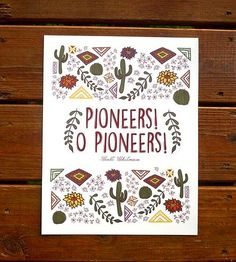 "Capturing the essence of the southwest in earthy hues, this quote art print features a line penned by Walt Whitman, ""Pioneers! O Pioneers!"" The text is printed large scale in the center of the piece, in rust-colored capital letters in a textured, quirky font. Top and bottom blocks are filled with desert plants and cultural ephemera, including saguaro cacti, geometric patterns and flowering succulents, all illustrated by hand."