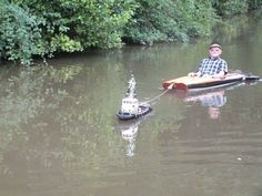 A Tiny Remote Controlled Tugboat Tows a Man in a Kayak Along a Canal in the…