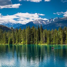 Photo by @susanseubert // Canoeing on peaceful Lac Beauvert at the Jasper Park Lodge with a view of Mt. Edith Cavell in the distance. The mountain was named in 1916 for Edith Cavell an English nurse executed by the Germans during World War I for having helped Allied soldiers escape from occupied Belgium. Photographed #onassignment for @natgeotravel about the #rockymountaineer #canada by natgeotravel