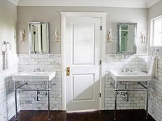 """The """"wow"""" factor in this master bathroom is the gorgeous Calacatta marble wainscot. The marble tile runs along the walls and acts as a backdrop behind the two console sinks."""
