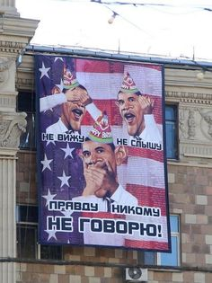 """On Obama's birthday, a banner depicting Obama as the """"Three Wise Monkeys"""" was  displayed across from the US. Embassy in Moscow."""