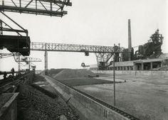 Tata Steel - Corus - Hoogovens Staalfabriek.  Erts (en ook kolen en kalksteen) wordt door kraan gelost en door grote transportkraan (midden) naar diverse opslagplaatsen vervoerd. IJmuiden, Velsen, Nederland, 1923. Links op de foto de vrije (sluisloze) toegangshaven voor zeeschepen, rechts de hoogoveninstallatie.