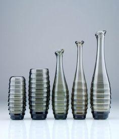 """Fünf Vasen """"Carola"""". Schwepnitz. 20. Jh.  Moosgrün getöntes Glas. Zwei Vasen mit leicht konvexer Form auf eingezogenem, massiven Stand. Wandung mit horizontalen, flachen Hohlkehlen. Drei Vasen mit kegelförmigem Korpus, der in eine glattwandig, spitz zulaufende Form mit wulstig abgeschrägtem Mündungsrand übergeht. Unterer Teil des Korpus ebenfalls mit flacher Hohlkehlenform. Ungemarkt. Entwurfsjahr: 1968 und 1969. Gebrauchsspurig. Minimale Spuren des Formprozesses in der Masse."""