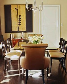 Black-lacquered chairs and a glass-topped table bring a sophisticated edge to this dining room - Traditional Home