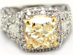 Custom designed engagement ring featuring a 4 carat radiant cut yellow diamond. Also, containing two trillion cut diamonds & 58 round cut diamonds - at Tower of Jewels