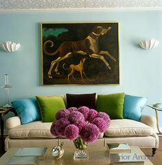 An early 18th century painting of English hounds hangs between a pair of plaster shell sconces above the sofa in the living room