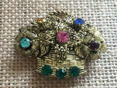A sweet flower basket brooch from the 1960's in pressed molded brass with multi colored rhinestones. Bright and colorful this brooch is made in the shape of a woven basket with flowers and leaves overflowing out the top. With five different colors...