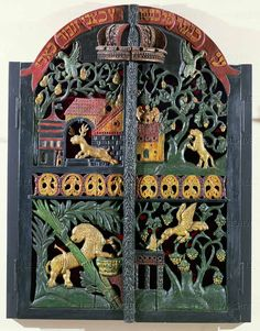 "Ark (Torah shrine) doors from the Butzian synagogue in Cracow, Poland. ""Be strong as a leopard, light as an eagle, fleet as a deer and strong as a lion to do the will of thy father,"" is inscribed over the doors. Carved and painted wood, 130 x 96 cm"