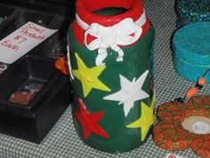 vase $15 - green with red, white & yellow stars. the white ribbon is hand made. this is a sauce jar recycled. can be made into any color or style.