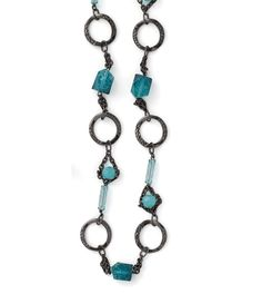 This necklace is the clear winner with a mix of hammered hematite rings, chain accents and varied shades of blue-green resin in geometric shapes.