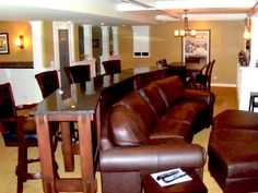 a large leather couch with custom bar height table behind.....great basement bar idea!