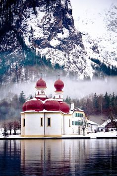 St. Bartholomä is a Catholic pilgrimage church in the Berchtesgadener Land district of Bavaria in Germany and is on the Konigssee River.  In the background is the eastern face of the Watzmann massif.  From 1697 onwards it was built in a Baroque style with a floor plan modelled on Salzburg Cathedral, two onion domes and a red domed roof.  by Andreea Nicola