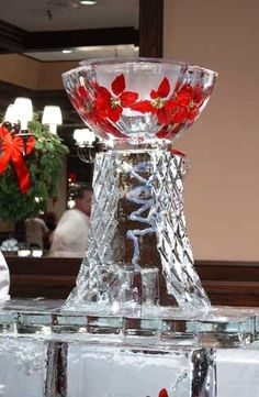 Punch bowl ice luge with poinsettias frozen into the bowl.