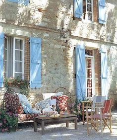 French country daybed with local Provençal fabrics: an inviting spot to take refuge from the heat of the day, near the stone walls of an old country house in Provençe.