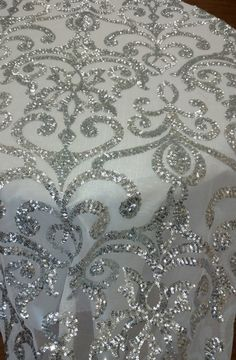 Sequins Lace Fabric to our fine line of fabric. If your new to fabric, sequins is a small, shiny disk sewn as one of many onto clothing for decoration making the consumer feel like the Belle Of The Ball. To begin with, this fabric starts off with a see through mesh backing accompanied by an damask pattern, sheer lace and scalloped edges. Along with the damask design there are shiny circular sequins that when hit with direct light, the sequins sparkle with an elegant shine. This popular…