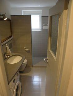 Koupelna je laděna do neutrální šedé barvy.