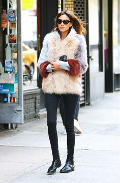 Alexa Chung wears a gray hoodie, colorblocked fur coat, black skinny jeans, patent leather ankle boots, and cat-eye sunglasses